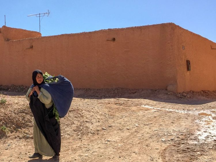 Woman returning from the fields Strength Heat Morocco Returning Home Labor Work One Person Standing Clear Sky Real People Outdoors Architecture Built Structure Day Sunlight Building Exterior