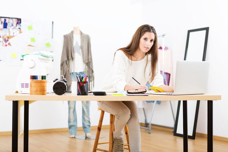 Young designer working in her desk for new designs Adult Business Businesswear Computer Day Design Professional Desk Fashion Designer Indoors  Laptop Occupation Office One Person People Skill  Small Business Table Technology Wireless Technology Women Working Young Adult