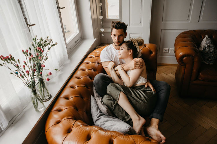 Rear view of couple sitting at home