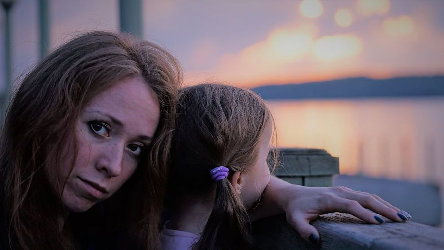 Close-up of woman with daughter during sunset