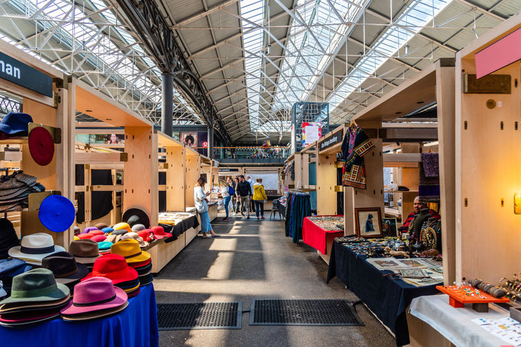 Old Spitalfields market with unidentified people. Independent stall holders showcasing handcrafted pieces. The market hosts arts and craft and street food market. Brexit Britain London Uk Antique Architecture Beautiful British Building Business City Culture Destination England English Europe European  Flea Food Foodie Gastro Handcrafted Interior KINGDOM Landmark Market Marketplace Merchandise Old People Retail  Retro Revival Shop Shopping Shoreditch Spitalfields Stall Store Street Street Food Tourism Tourist Town Travel Vintage Whitechapel