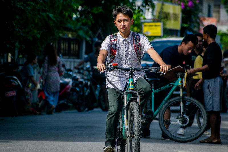 Portrait of people riding bicycle on road