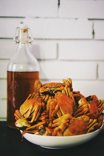 Close-Up Of Cooked Crabs By Drink On Table