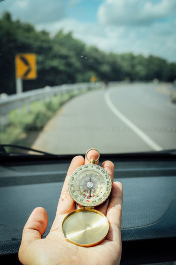 Compass in the hand Compass In The Hand Car Car Interior Day Direction Finger Focus On Foreground Hand Holding Human Body Part Human Finger Human Hand Lifestyles Mode Of Transportation Motor Vehicle One Person Outdoors Personal Perspective Real People Road Transportation Vehicle Interior