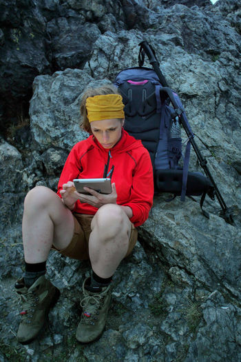caucasian female hiker using portable tablet technology outdoors on a alpine hiking trail Alpine Backpacking Camping Expedition Freedom Hiking Tablet Travel Trekking Woman Youth Activity Adventure Battery Communication Connection Day Female Front View Full Length Hobby Internet Leisure Activity Lifestyles Nature Navigation One Person Outdoors People Portable Information Device Real People Rock Rock - Object Rock Formation Sitting Solid Technology Trail Wireless Technology Young Adult