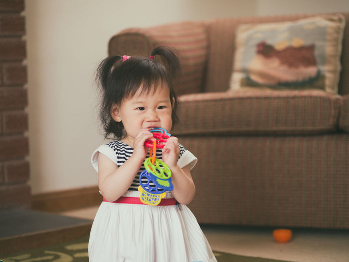 Cute girl biting toy while standing at home