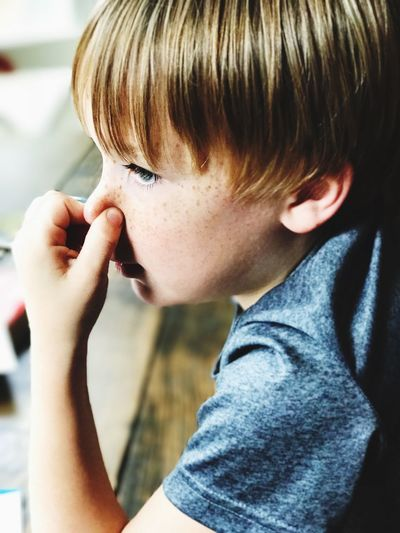 Close-up of boy holding nose