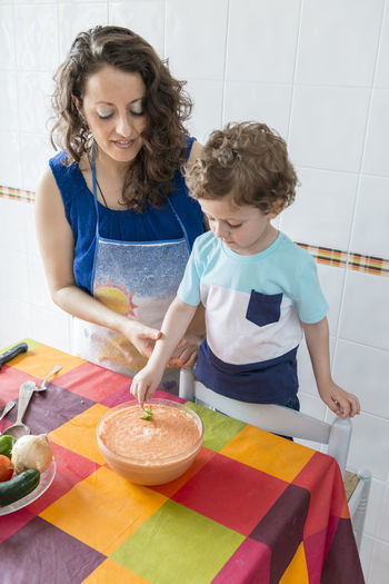 High angle view of mother and daughter in kitchen