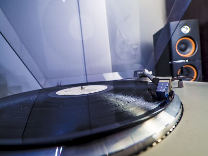 Close up view of old fashioned turntable playing a track from black vinyl with light bluish interior lightning Arts Culture And Entertainment Close-up Day Gramophone Indoors  Music Musical Instrument No People Old-fashioned Record Record Player Needle Retro Styled Technology Turntable