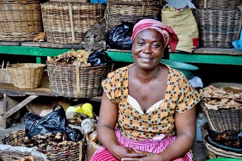 Portrait of female vendor smiling while sitting against wicker baskets at market