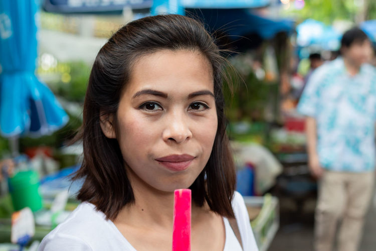 Close-up portrait of woman having pink popsicle outdoors