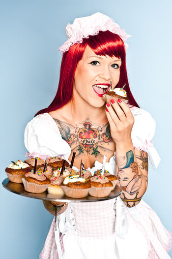 Young rockebella styled women eats cupcakes Studio Shot Portrait One Person Young Adult Indoors  Beautiful Woman Beauty Food And Drink Looking At Camera Women Young Women Adult Sweet Food Food Sweet Happiness Temptation Hairstyle Rockebilly 50s Alternative Lifestyle Cupcakes Red Hair Inked