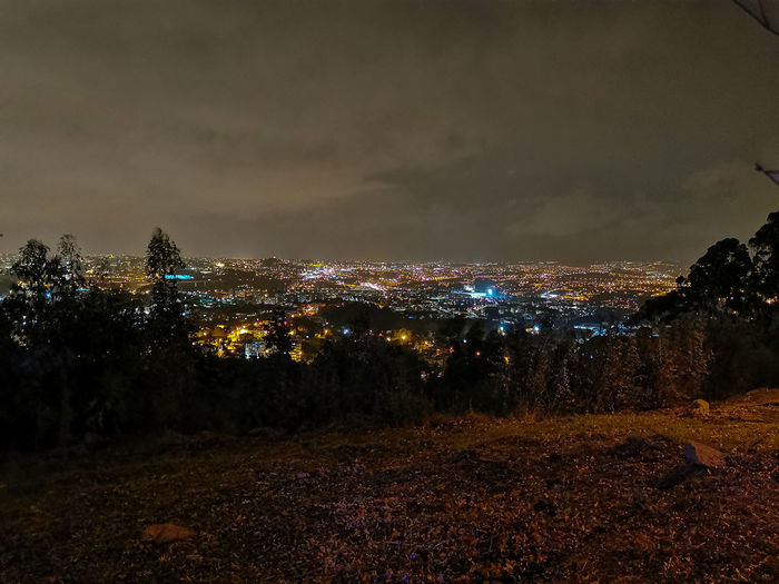 Illuminated city on field against sky at night