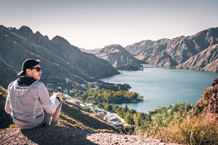 Man sitting on mountain by lake against sky