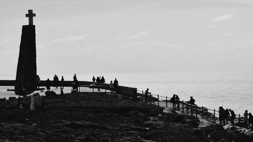The Cross and the People People Silhouettes Scenic Lookout Portugal_em_fotos Cabo Da Roca. Sintra Cabo Da Roca Outdoor Photography Scenic Landscapes Black And White Photography Monochrome Black & White Black And White Silhuettes Shadows & Lights People_bw Outdoors Week On Eyeem Week Of Eyeem The EyeEm Magazine EyeEm Gallery Weekend Snaps Portugal Tourist Destination Tourist Attraction
