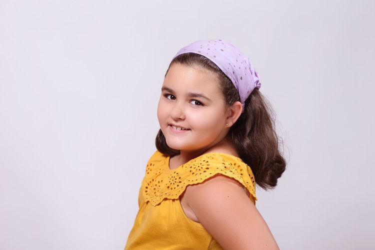 Portrait of smiling girl against white background