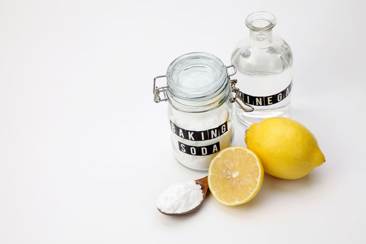 baking soda in the glass container with lemon Alkaline Anti Inflammatory Baking Soda Bicarbonate Clear Sky Close-up Cooking Glass Container Heart Burn Ingredient Jar Label Lemon Medicine Neutralizer Portrait Sodium Bicarbonate Spoon Spoonful Vinegar White Background White Vinegar