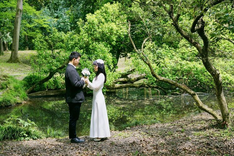 Waterfront Bride And Groom Couple Tree Wedding Real People Plant Newlywed Couple - Relationship Standing Wedding Dress Togetherness Two People Married Emotion Love
