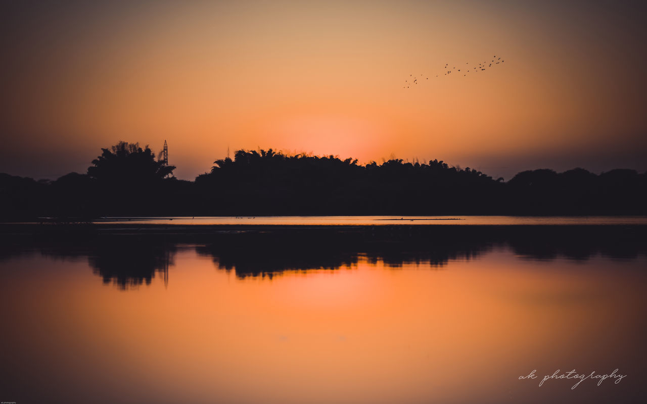 sunset, reflection, silhouette, nature, orange color, beauty in nature, scenics, lake, tranquil scene, water, tranquility, sky, tree, sun, no people, outdoors, clear sky