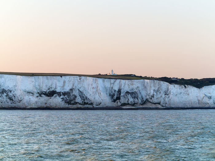 White cliffs by sea against clear sky