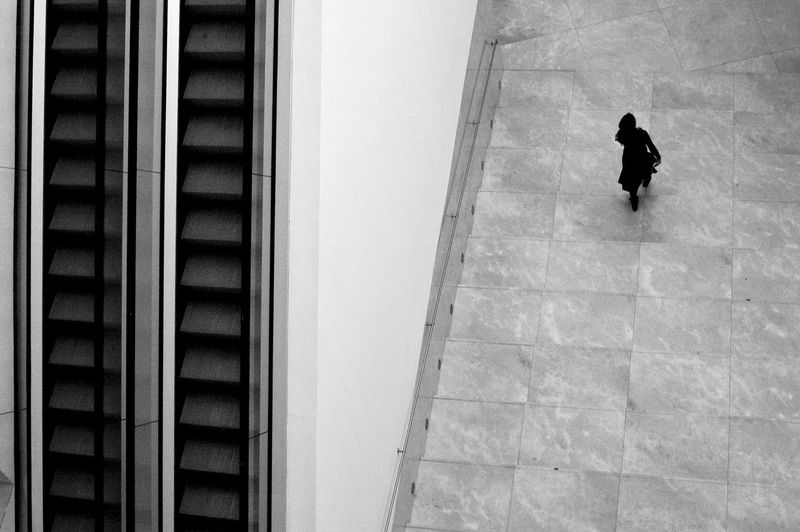 High Angle View Of Woman By Escalators In Shopping Mall