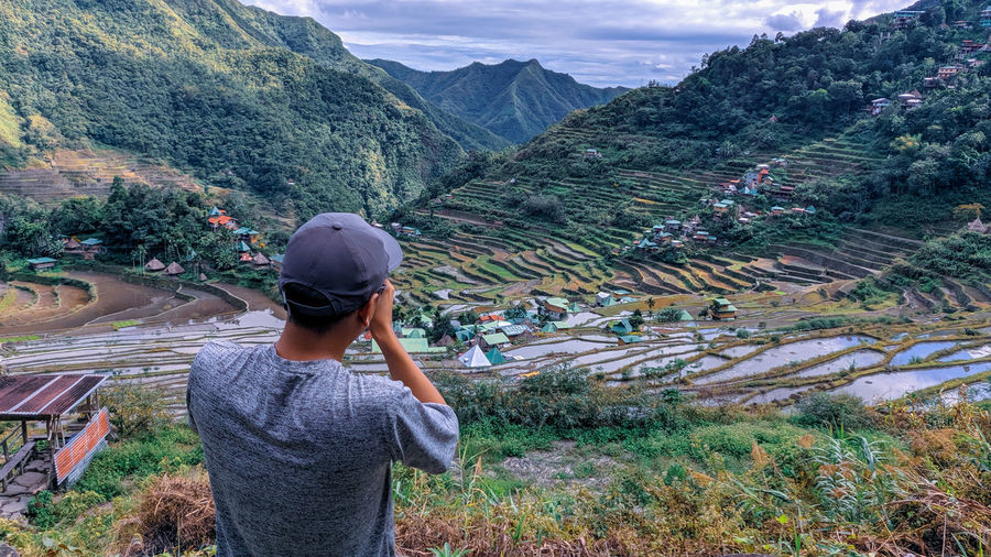 Rear view of man taking a photo of mountains