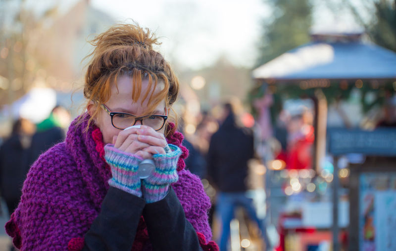 Portrait of woman drinking tea at market during winter