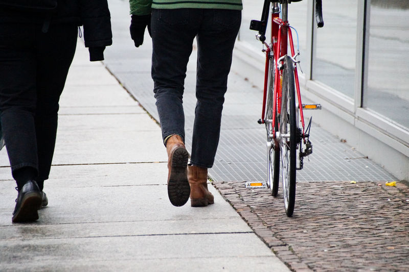 Low section of men walking with bicycle