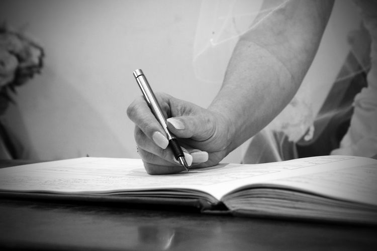 Cropped hand of bride writing on book at table