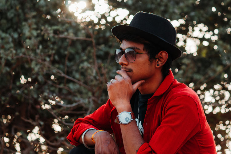One Person Glasses Real People Leisure Activity Young Men Focus On Foreground Lifestyles Young Adult Looking Sunglasses Looking Away Clothing Headshot Fashion Tree Hat Day Casual Clothing Plant Outdoors Contemplation