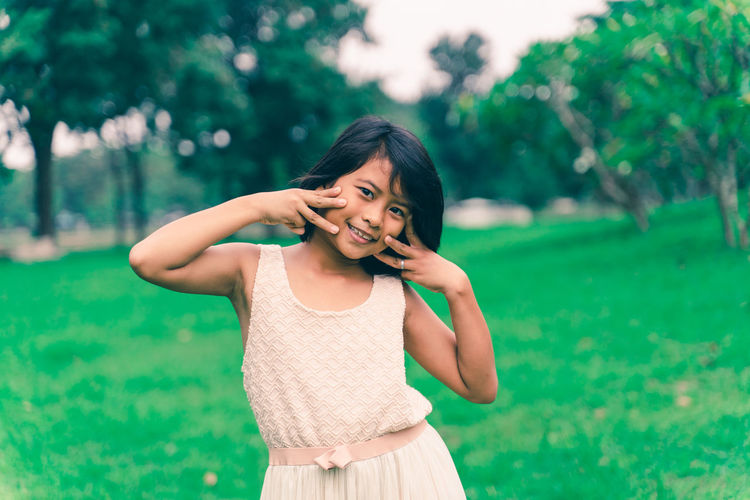 Portrait of smiling girl standing at park