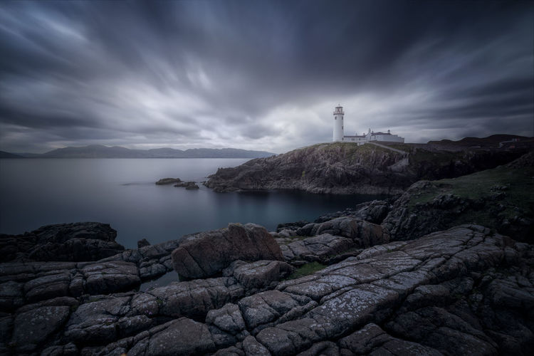 Fanad Head Lighthouse in Ireland Lighthouse Lighthouse Lovers Lighthousephotography Landscape Colour Low Angle View Ireland Fafnad Head Cloudy Blue Moody Sky Light Rock Formation