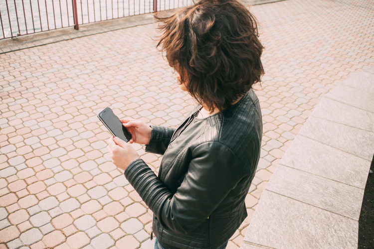 Midsection of woman using mobile phone while standing on cobblestone