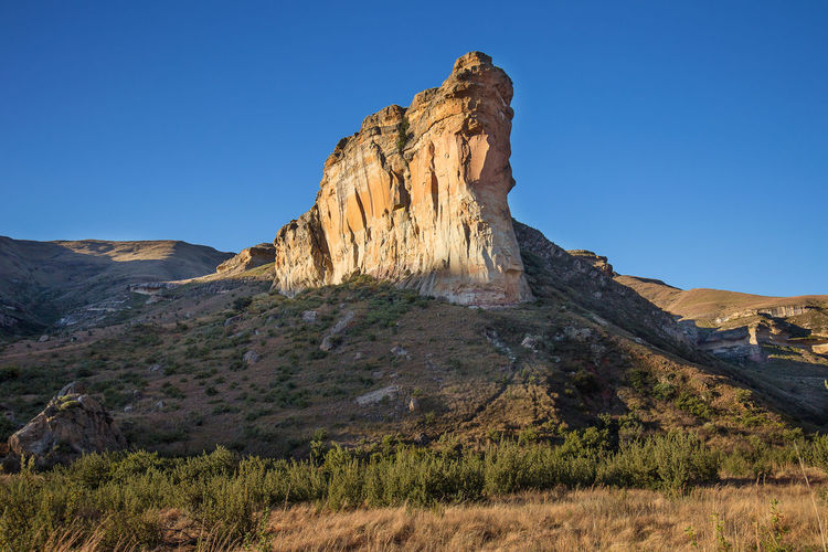 The famous Brandwag Buttress stands guard at the entrance to the Golden Gate National Park, Clarens, Free State, South Africa Brandwag Buttress Clarens Free State Arid Climate Beauty In Nature Brandwag Clear Sky Day Environment Formation Golden Gate National Park Grass Land Landscape Mountain Mountain Peak Nature No People Outdoors Rock - Object Rock Formation Scenics - Nature South African Mastiff Tranquil Scene Tranquility