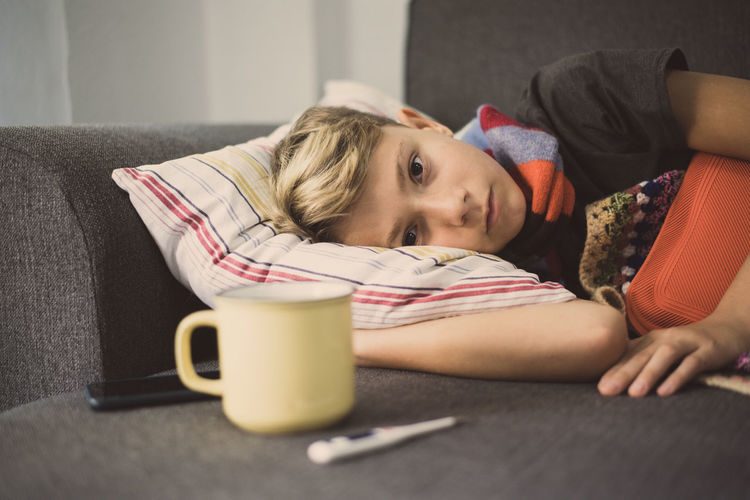 Portrait of ill boy lying on sofa at home