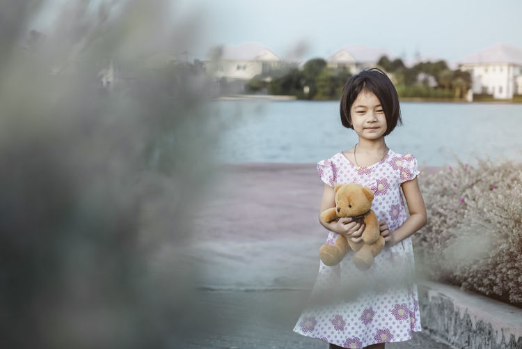 A portrait of a one happy girl standing by lake. She is holding cute little teddy bear in her hands. Cute child concept. Asian  Little Girl Environment Nature Kid Kids Lifestyles Happiness Happy Child Childhood Global Warming Outdoor Playing Teddy Bear Holding Leisure Smile Landscape House Village Young Lovely Save Earth