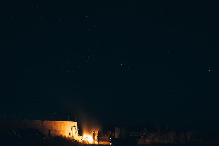 People standing by bonfire against sky at night