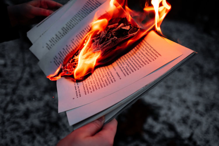 Close-up of hand holding burning book