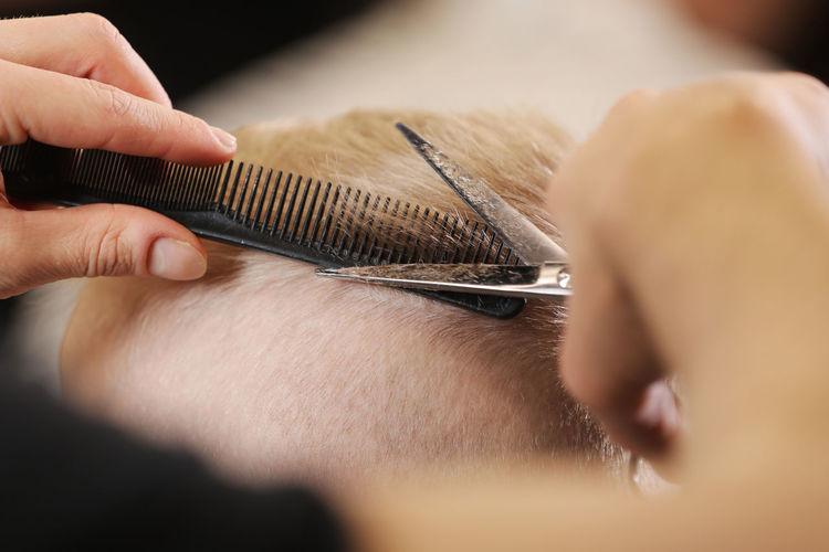Cropped hands cutting man hair