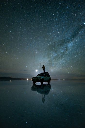 Silhouette man standing on car at beach against star field during night
