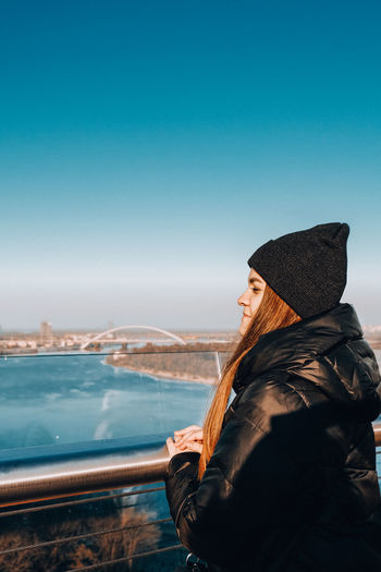 Side view of smiling woman looking away while standing against sky