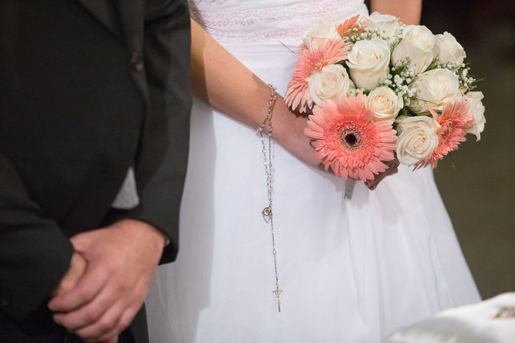 Midsection of bride and bridegroom standing during wedding