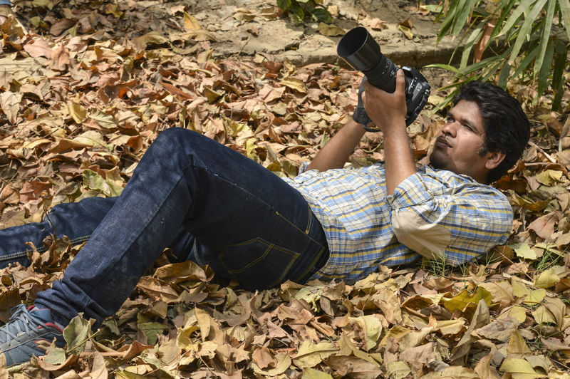Full length of young man lying down on road