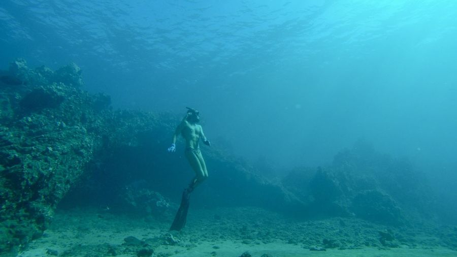 Long haired man freediving 40 feet below the seas surface