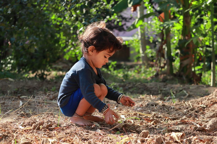 Side view of boy playing in the garden with sand