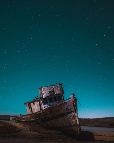 Abandoned boat against starry blue sky at night