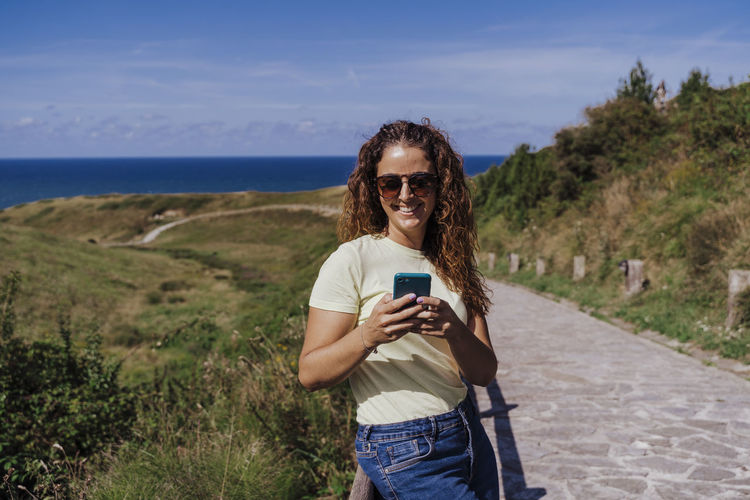 Portrait of smiling young woman using mobile phone against sky