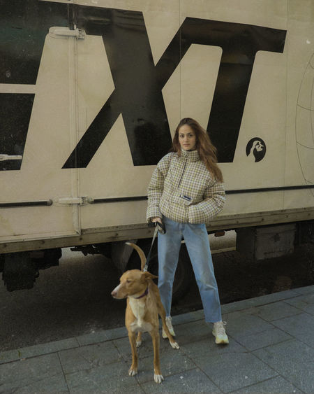 Portrait of woman with dog standing outdoors