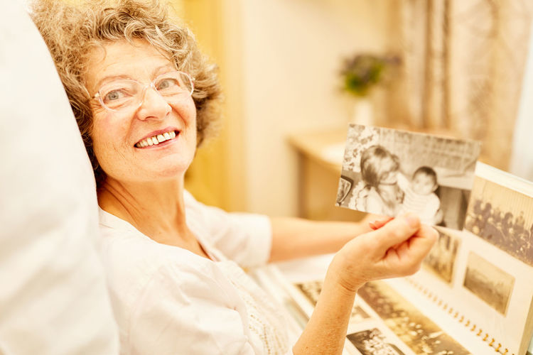 Portrait of smiling woman holding old photograph while sitting at home