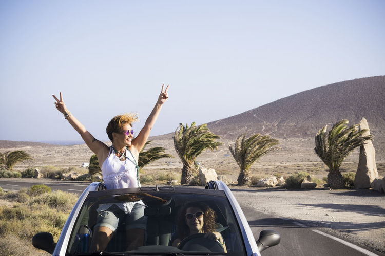 Couple of happy woman enjoy the trip traveling by car - driving and standing outside the roof with success and happiness pose - vacation in outdoor tropical place for cheerful people Mother Freedom Horizon Over Water Landscape Horizontal Format Cheerful Couple Two People On The Beach Caucasian Casual Clothing Hippie Transportation Car Mode Of Transportation Motor Vehicle Real People Sky Arms Raised Sunlight Nature Human Arm Land Vehicle Lifestyles Clear Sky Leisure Activity Road Day Women Road Trip Outdoors Two People Curly Hair Palm Tree Coastline Island Adventure Togetherness Friends Females Vacations Traveling Driving Success 40-44 Years Mountain Range Relaxation Bonding